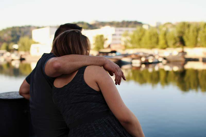 Latin American couple embracing and sitting beside water