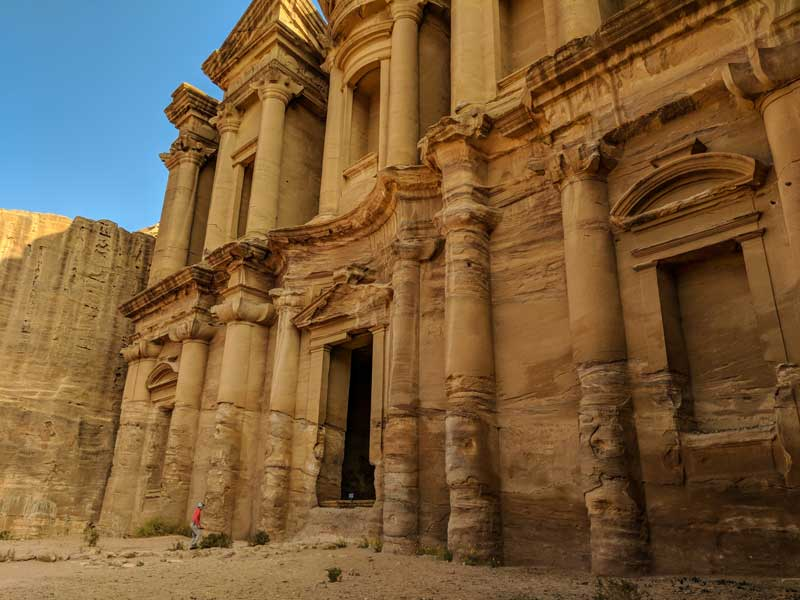 The huge cathedral of Petra with people walking in the door