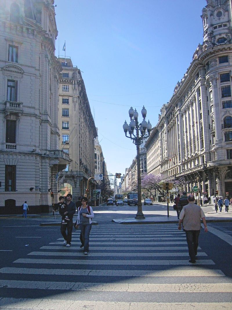 Buenos Aires street with people lamposts and cars