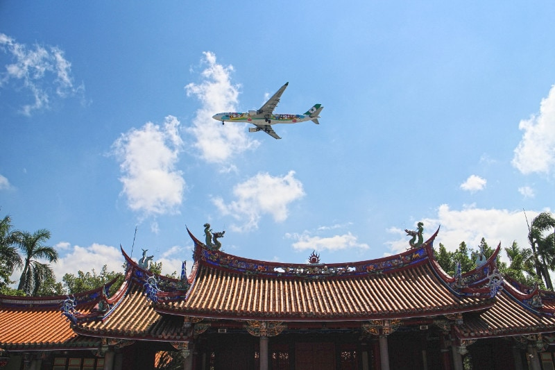 A plane flying over temple and landing in taoyuan airport