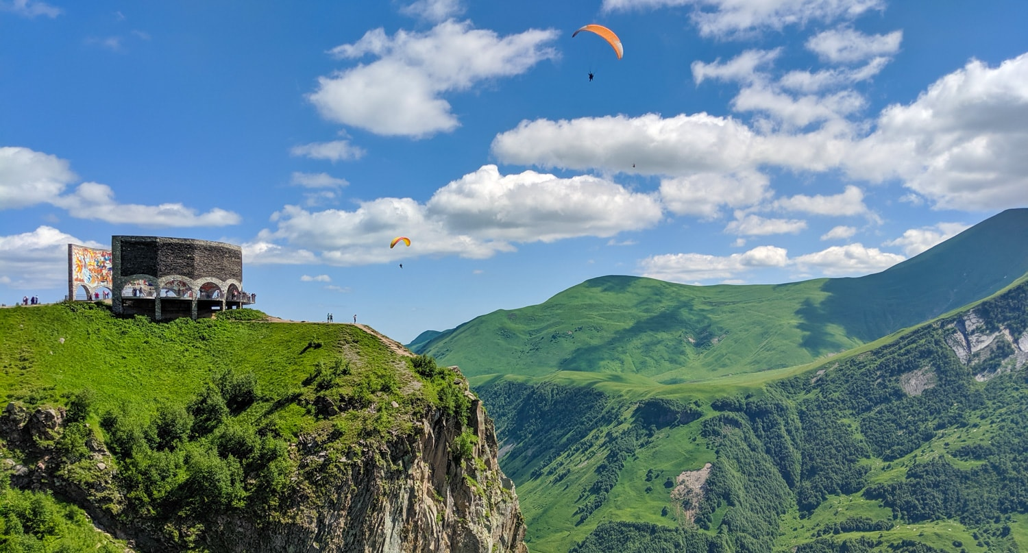 Paragliders near the Gudauri viewing point and Russia-Georgia Friendship Monument