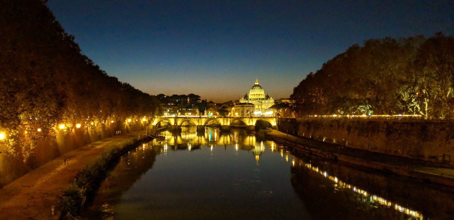 St Angelo Bridge Ponte Sant'Angelo at night with st Peters basilica in the background