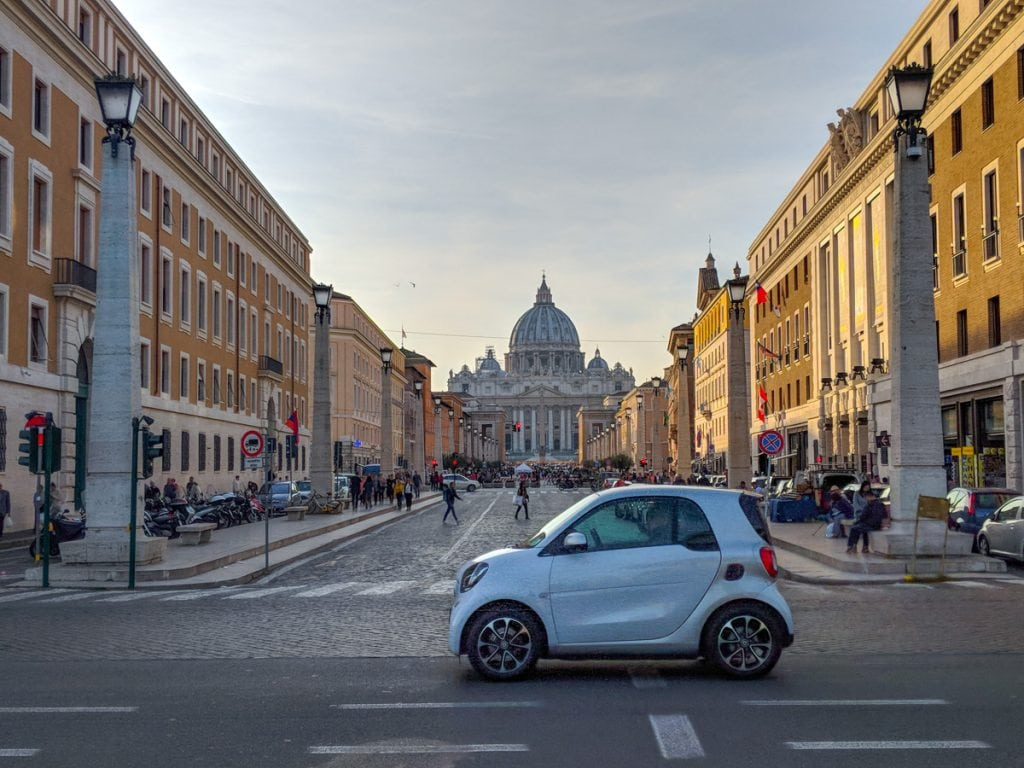 A car passes the Piazza Pia in front of St. Peter's Basilica